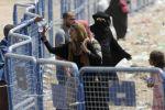 Syrská žena se svými dětmi čeká za bezpečnostními …